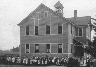 The first Harney School was built and named for Lt. General William S. Harney. Students are standing in front of school.