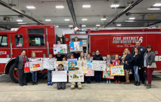 Students display their prize-winning posters on fire safety